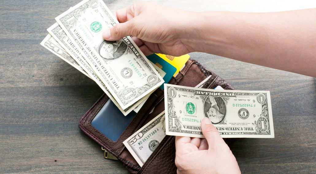 A wallet with dollar bills being held near it